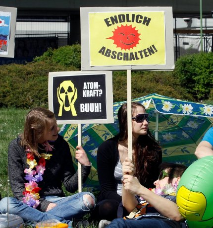 People demonstrate during a public summer party calling on authorities to switch off atomic power plants in front of the International Center where the International Atomic Energy Agency, IAEA, has it's headquarters in Vienna, Austria, Saturday, April 9, 2011. Poster at right reads: Finally Switch Off. Poster at left: Nuclear Power, Booh.